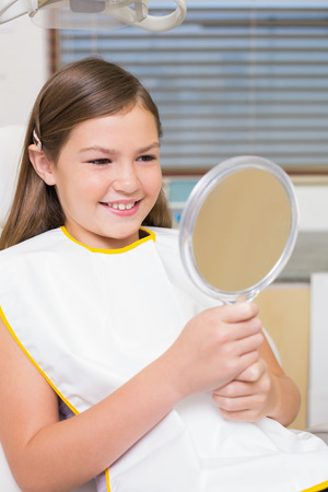 Little girl holding mirror in dentists chair at the dental clinic photo