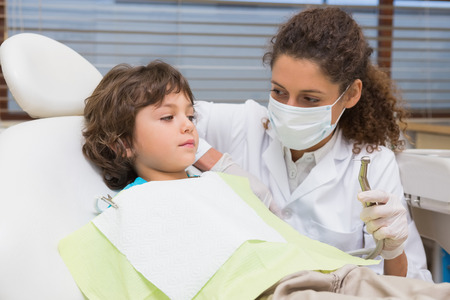 Pediatric dentist showing little boy in chair the drill at the dental clinic photo