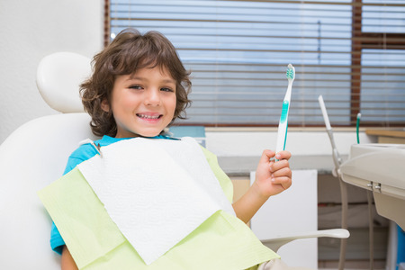 Little boy in dentists chair holding toothrbrush at the dental clinic photo