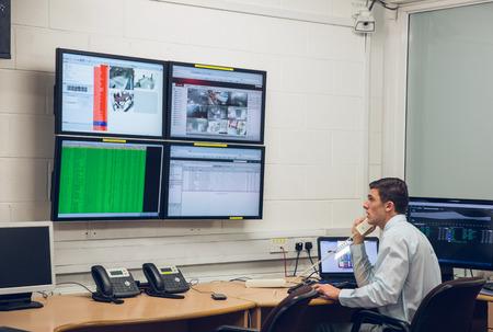 computer centre: T�cnico sentado en el diagn�stico de funcionamiento de la oficina en el gran centro de datos