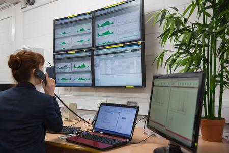 Technician sitting in office running diagnostics in large data center 免版税图像
