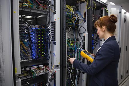 computer centre: T�cnico feliz usando analizador de cable digital en el servidor en el gran centro de datos