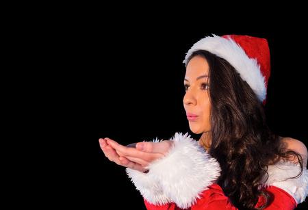 pere noel sexy: Jolie brunette � santa tenue soufflant sur ses mains sur fond noir Banque d'images