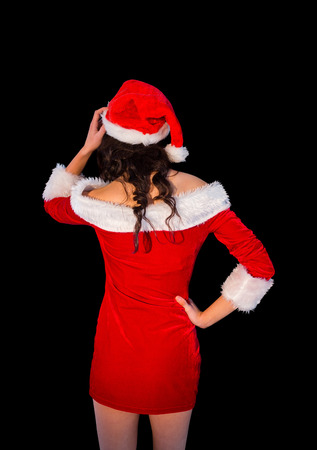 pere noel sexy: Penser brune � santa costume posant avec la main sur la hanche sur fond noir