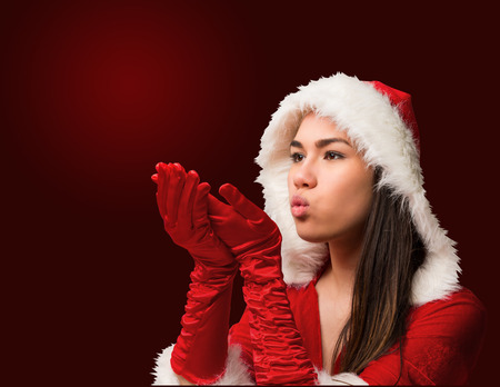 Pretty brunette in santa outfit blowing over hands on red vignette background photo