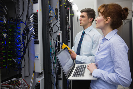 data: Team of technicians using digital cable analyser on servers in large data center
