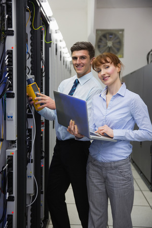 data storage: Team of technicians using digital cable analyser on servers in large data center