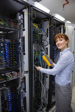 maintaining: Technician using digital cable analyzer on server  in large data center