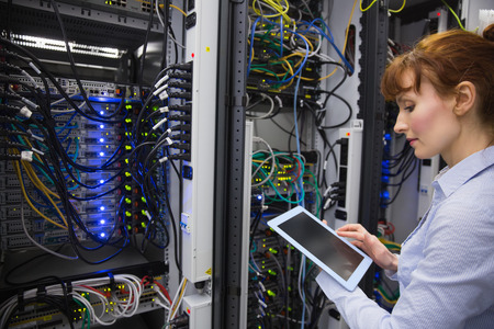 technician: Technician using tablet pc while analysing server in large data center Stock Photo