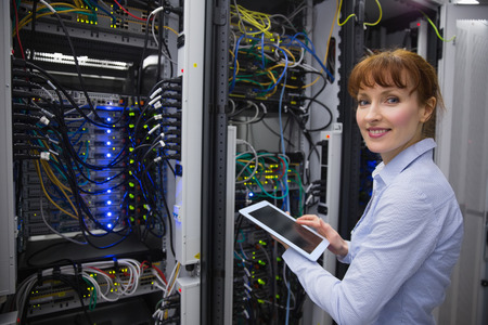 computer repairing: Smiling technician using tablet pc while analysing server in large data center Stock Photo