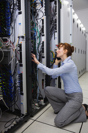 Serious technician talking on phone while analysing server in large data center photo