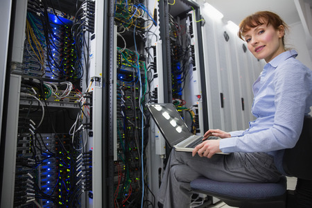swivel chair: Technician sitting on swivel chair using laptop to diagnose servers in large data center