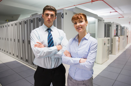 computer programmer: Confident data technicians looking at camera  in large data center