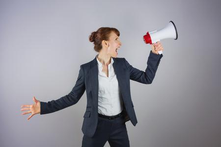 Smiling businesswoman shouting through megaphone on grey background photo
