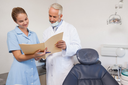 Dentist and assistant looking at file together at the dental clinic photo