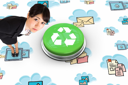 Serious businesswoman bending against recycling symbol photo