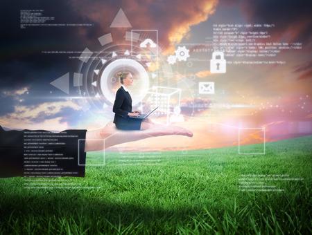Businesswoman using laptop against green field under orange sky photo