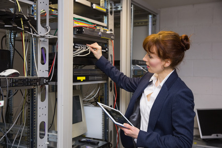 Pretty technician using tablet pc while fixing server in large data center photo