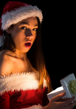 Amazed brunette in santa outfit opening a gift on black background photo