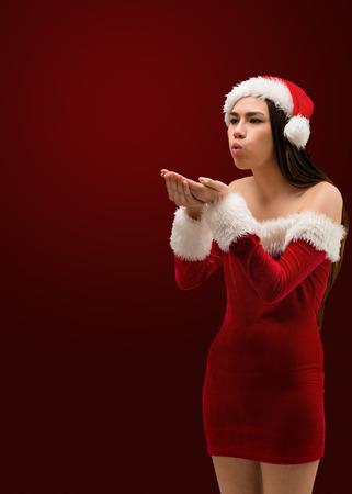 pere noel sexy: Jolie brunette � santa tenue souffler sur les mains sur le rouge vignette fond