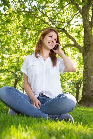 Pretty redhead on the phone in the park on a sunny day photo