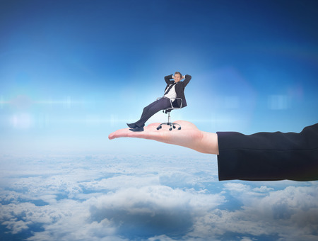 Businessman relaxing in swivel chair against blue sky over clouds at high altitude photo