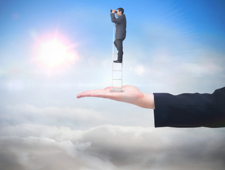 Businessman standing on ladder against blue sky with sunshine and clouds photo