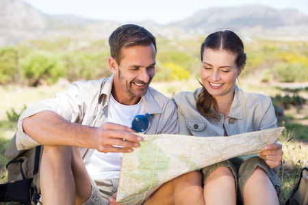 Happy hiking couple reading the map on mountain trail on a sunny day photo