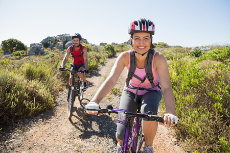 bike helmet: Active couple on a bike ride in the countryside on a sunny day