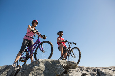 adventuring: Active couple on a bike ride in the countryside on a sunny day