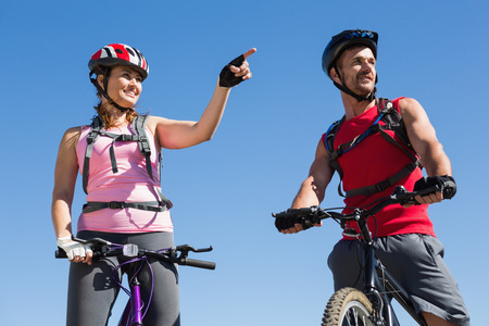 Fit cyclist couple standing at the summit on a sunny day photo