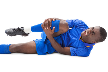 Injured football player lying on the ground on white background photo