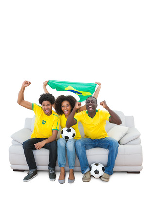 Brazilian football fans in yellow cheering on the sofa on white background photo