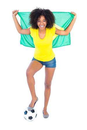 Fan de football Jolie tenue brésilien drapeau acclamations à la caméra sur fond blanc