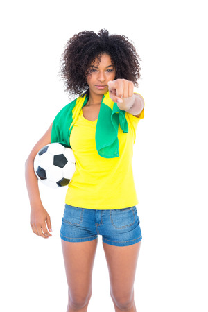 Pretty football fan holding brazilian flag pointing at camera on white background photo
