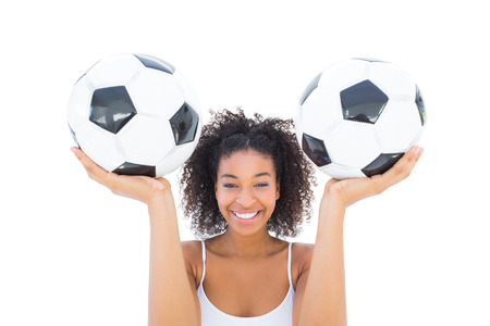 Pretty girl holding footballs and smiling at camera on white background photo