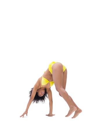 yellow bikini: Fit ragazza in bikini giallo flessione su sfondo bianco