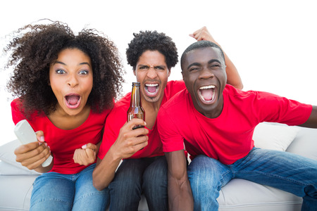 Football fans in red cheering on the sofa with beers on white background photo