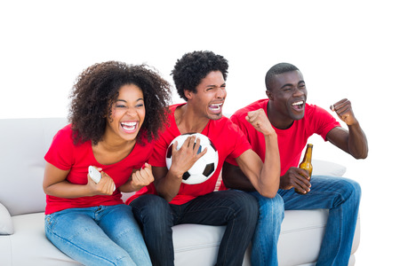 Cheering football fans in red sitting on couch on white background photo