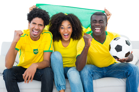 Excited football fans in yellow sitting on couch with brazil flag on white background photo