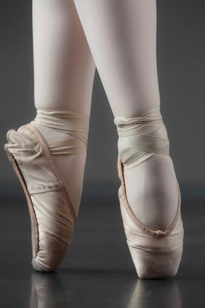 zapatillas ballet: Bailarina que se coloca en punta en zapatillas de ballet en el estudio de ballet