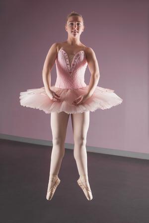 Graceful ballerina dancing en pointe in the ballet studio photo