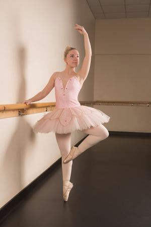 Beautiful ballerina standing en pointe holding barre in the dance studio photo