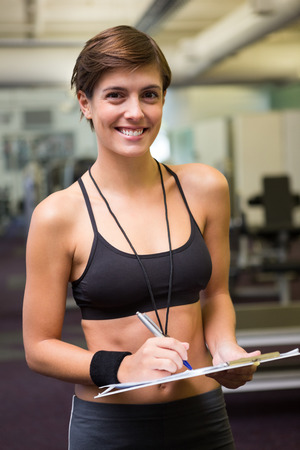 Fit trainer taking notes and smiling at camera at the gym photo