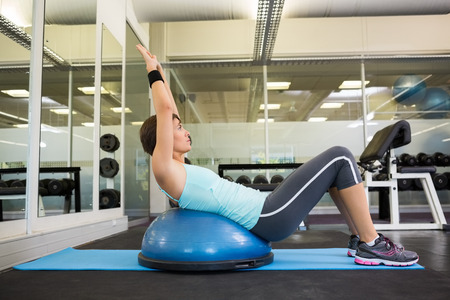 Fit brunette using bosu ball to work out at the gym photo