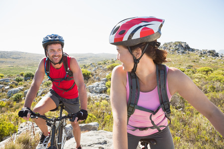 adventuring: Fit cyclist couple riding together on mountain trail on a sunny day