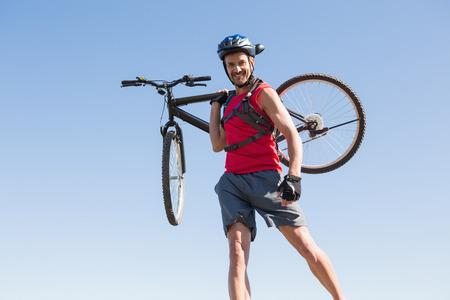 adventuring: Fit cyclist carrying his bike on rocky terrain on a sunny day Stock Photo