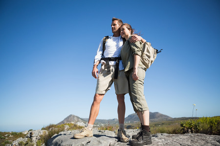 adventuring: Hiking couple looking out over mountain terrain on a sunny day