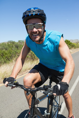 open road: Smiling cyclist riding on the open road on a sunny day Stock Photo