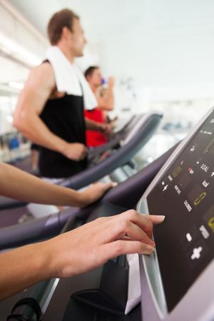 Row of people working out on treadmills at the gym photo